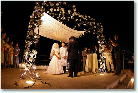 The wedding ceremony takes place under the chupah which is a canopy on four
